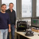 Forscher mit 3D-Drucker und Material.