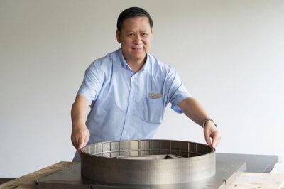 Professor Zhang Zhengwen mit 3D-gedrucktem Bauteil