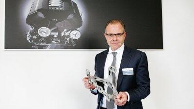 Leiter des Leiter des Audi Kompetenzcenters Anlagen- und Umformtechnik, Jörg Spindler, mit 3D-gedrucktem Bauteil.
