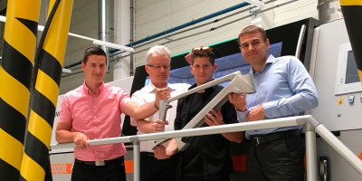 Mitarbeiter mit Fahrradrahmen vor Concept Laser X Line 2000R 3D-Drucker.