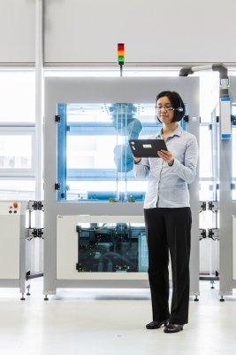 Mitarbeiterin analysiert mit Tablet und App Daten eines Gerätes.
