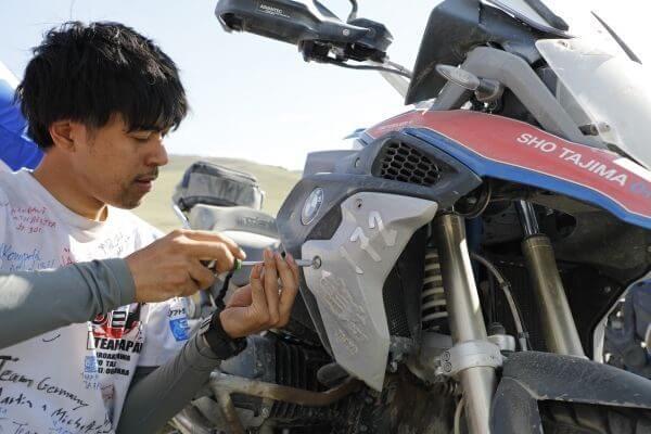 Teilnehmer schraubt Kühlerabdeckung auf sein Motorrad