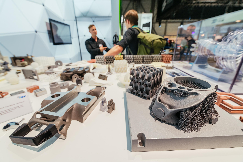 Impressionen von der Messe, zwei Personen im Hintergrund, im Vordergrund mehrere 3D-gedruckte Teile