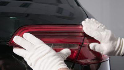 weiße Handschuhe zu sehen, die ein Rücklicht auf einen Audi befestigen