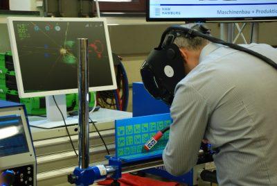 Ein Student vor dem virtuellen Schweißgerät bei der Arbeit