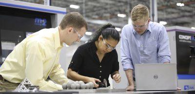 Drei Mitarbeiter arbeiten mit handlichem Werkzeug an kleinen Objekten