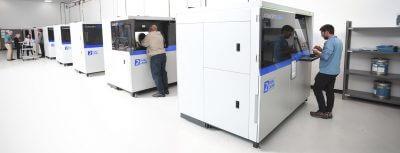 Je eine Person steht vor einem großen 3D-Drucker