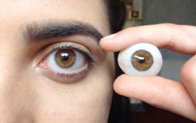 Frau mit künstlichem Auge in der Hand