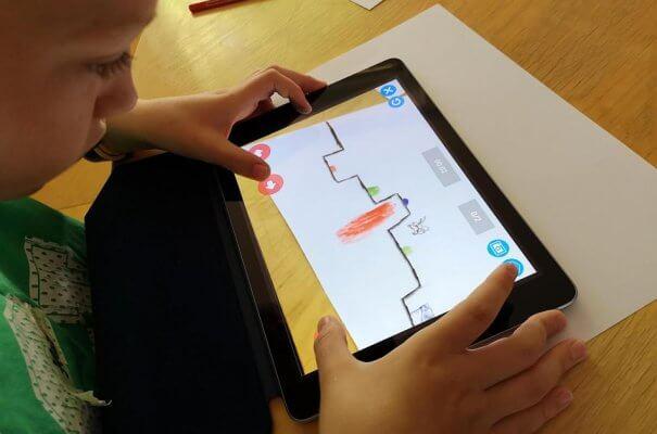 Kind mit Tablet beim Entwerfen eines Spiels