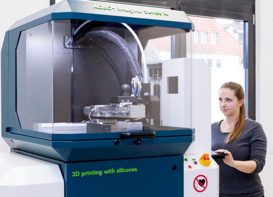 Frau bedient 3D-Drucker für Silikon