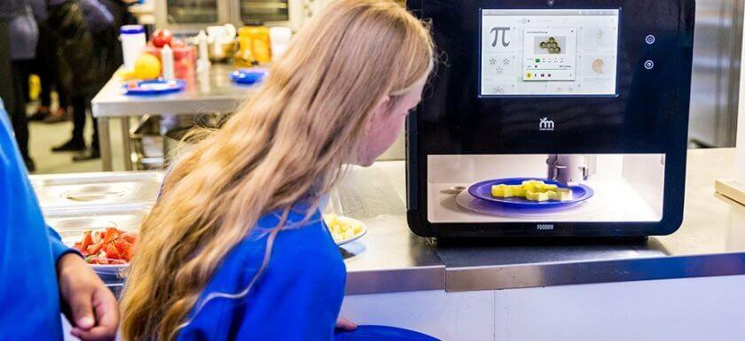 Kind steht vor Lebensmitteldrucker an der Big Bang Messe
