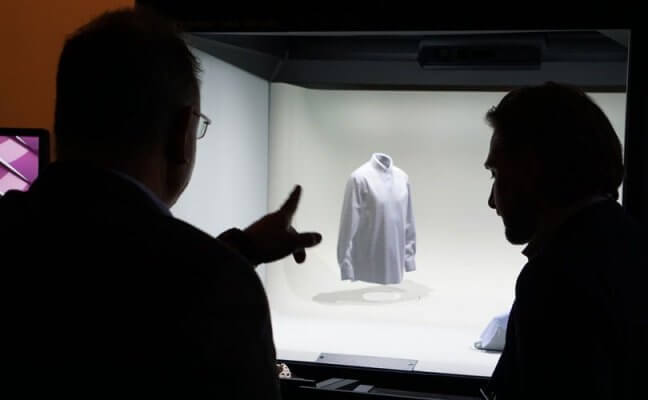 Mitarbeiter betrachten Modell eines Hemdes