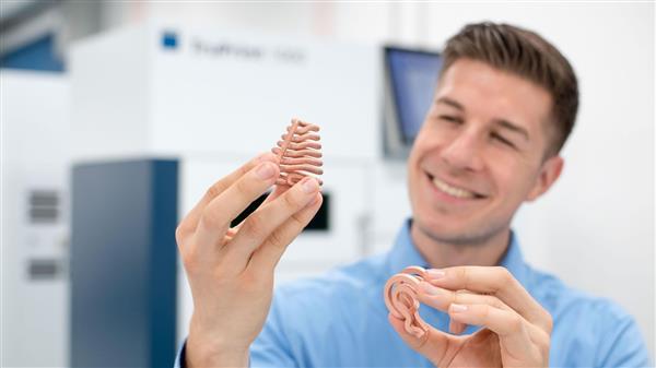 Mann mit 3D-gedruckten Objekten aus Kupfer in den Händen