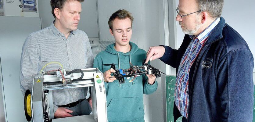Schüler und zwei Lehrer mit der teilweise 3D-gedruckten Drohne