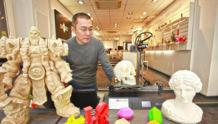 Mitarbeiter vor 3D-gedruckten Objekten