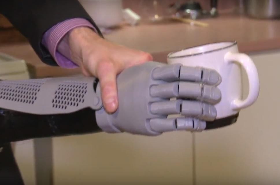 Gründer hält Prothese, die Tasse hält