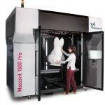 Frau nimmt Objekt aus Massivit 1800 Pro 3D-Drucker