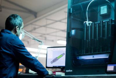 Mitarbeiter neben dem 3D-Drucker