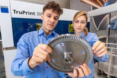 TRUMPF 3D-Drucker und Turbinenschaufelrad und zwei Mitarbeiter