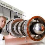 Mann prüft 3D-gedrucktes Metallobjekt