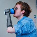 Mann hält Becher mit 3D-gedruckter Prothese
