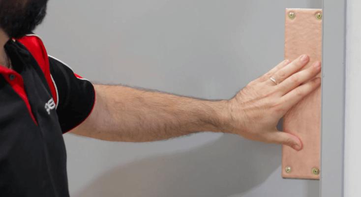 Mann hält Hand an Türplatte