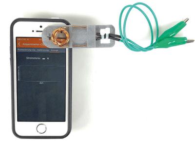 Smartphone mit Clip und Spule dran
