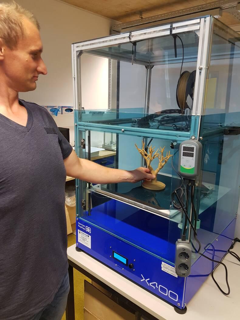 Mann mit Objekt aus dem 3D-Drucker