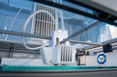 3D-Drucker und TÜV SÜD Schild