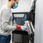 Mann mit 3D-gedruckten Teilen an 3D-Drucker