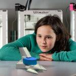 Kind sitzt vor drei 3D-Druckern