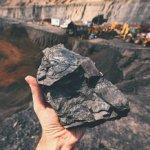 Ein großes Stück Kohle in der Hand
