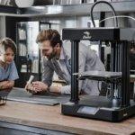 Vater und Sohn neben 3D-Drucker
