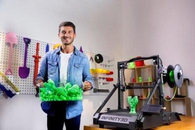 3D-Drucker Infinity3D mit Mann, der Kiste mit vielen gleichen Objekten hält